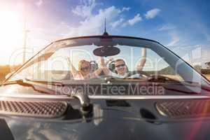 Hurra, wir haben Urlaub - Pärchen im Cabrio hebt die Arme hoch vor Glück