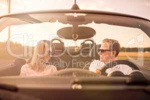 Pärchen im Cabrio schaut sich verliebt an - Liebespaar im Cabrio in Frontansicht