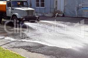 Water truck watering the asphalt at a manufacturing plant for du
