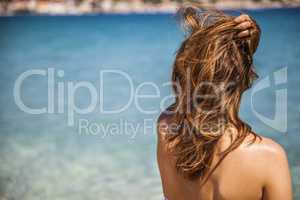 long blonde red hair girl wathckng at the sea with a hand over h
