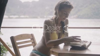 Pretty young woman wearing bikini sitting on the bench and reading book during her holiday in slow motion.