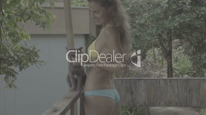 Pretty young woman wearing bikini standing and playing with cat on the terrace in slow motion.