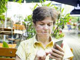 Woman with smartphone sitting in the beer garden