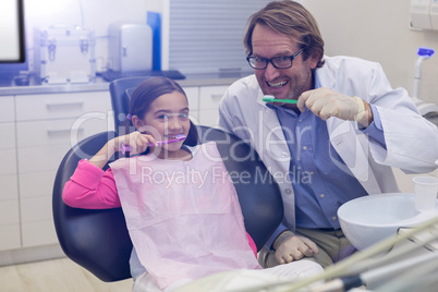Smiling dentist and patient brushing their teeth
