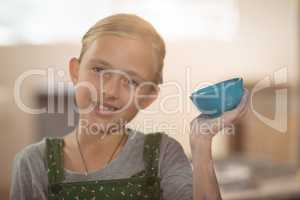 Portrait of girl showing bowl in pottery workshop