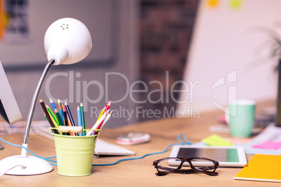 Digital tablet, spectacles and penholder on a table