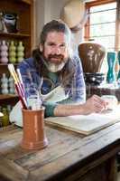 Portrait of male potter in pottery workshop