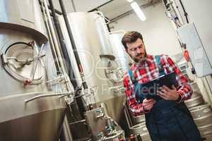 Manufacturer holding writing pad in brewery