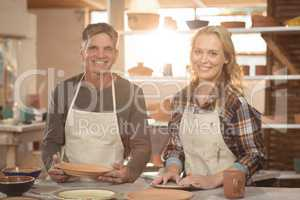 Smiling potters working together in pottery workshop