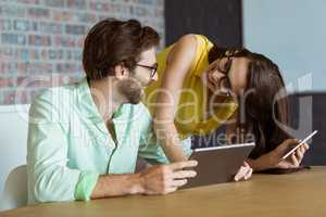 Business executive and co-worker interacting while using digital