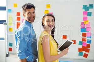 Business executive and co-worker smiling and holding digital tab