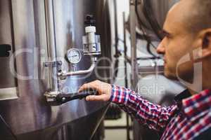 Manufacturer adjusting pressure gauge in brewery