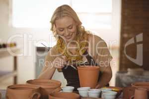 Beautiful female potter painting on pot