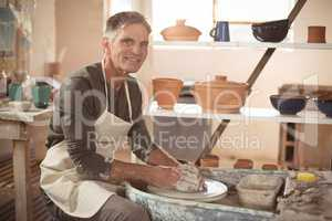 Smiling male potter making pot in pottery workshop