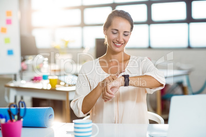 Female business executive adjusting time on her smartwatch