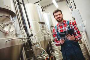 Portrait of manufacturer holding writing pad in brewery