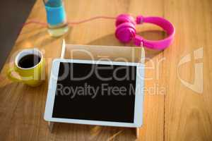 Digital tablet, headphones and a cup of coffee on table