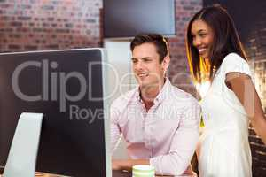 Businesswoman interacting with coworker while working on compute