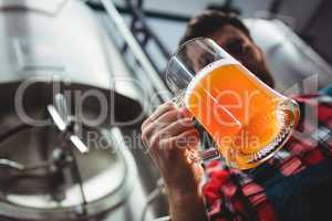 Manufacturer examining beer glass