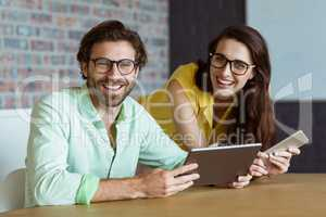 Portrait of business executive and co-worker holding digital tab