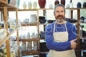 Happy male potter standing in pottery workshop