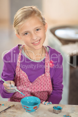 Smiling girl painting on bowl in pottery workshop