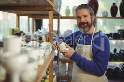 Smiling male potter holding cup in pottery workshop