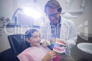 Dentist showing young patient how to brush teeth