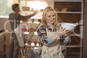 Female potter checking bowl in pottery workshop