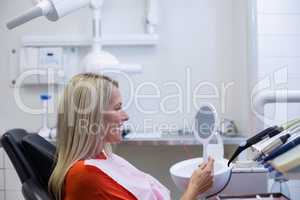 Patient checking her teeth in mirror