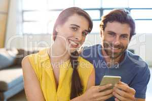 Female business executive showing mobile phone to co-worker