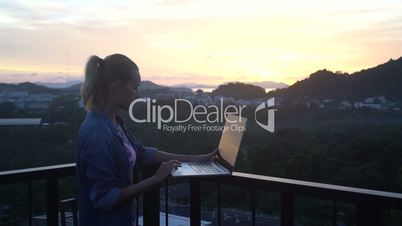 Side view of pretty blonde woman in bikini bra and jeans shirt working on a laptop computer while standing on a rooftop over beautiful sunrise. Freelance and technology