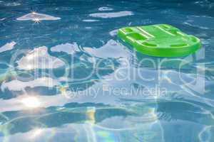 Green lifesaver floating in a swimming pool