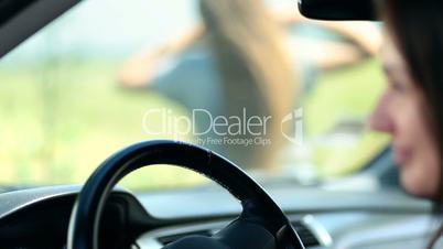 Woman's hand sliding on car's steering wheel