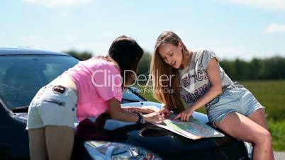 Cute women using map on a roadtrip for direction