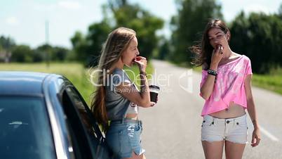 Young women eating and drinking coffee near car