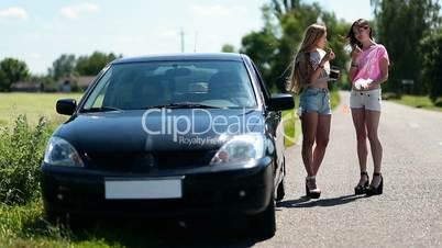 Beautiful girls having a snack on a roadside