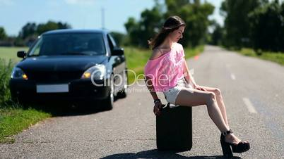 Lovely woman sitting on canister on country road