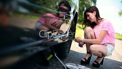 Attractive girl trying to remove wheel with wrench