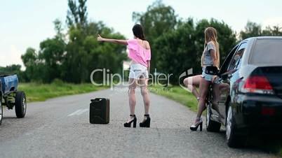 Young women hitchhiking near broken car