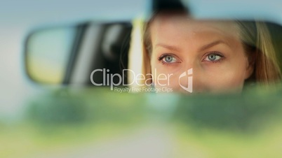 Reflection of woman's blue eyes in rearview mirror