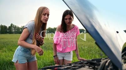 Cute women standing near opened hood of broken car