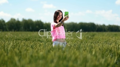 Sexy woman making a self portrait in the field