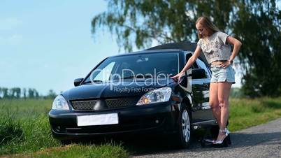 Pretty girl inflating car tyre with foot pump