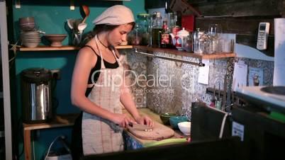 Charming woman chopping garlic on wooden board