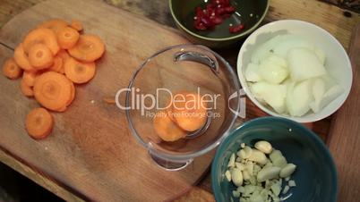 Woman adding sliced carrot into a glass bowl