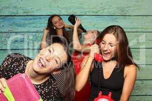 Glückliche Mädchen vor einer Fotobox - Photobooth mit Telefon und Geschenk