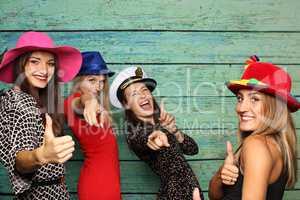 Frauengruppe vor Fotobox zeigen Daumen hoch und lachen - Photobooth