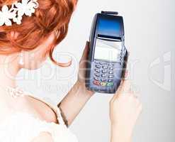 The concept of electronic payment. Closeup a beautiful bride holding credit card over pos terminal