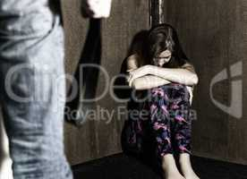 frightened woman sitting in the corner with a faceless man holding belt, conceptual shoot portraying process and effects of domestic violence